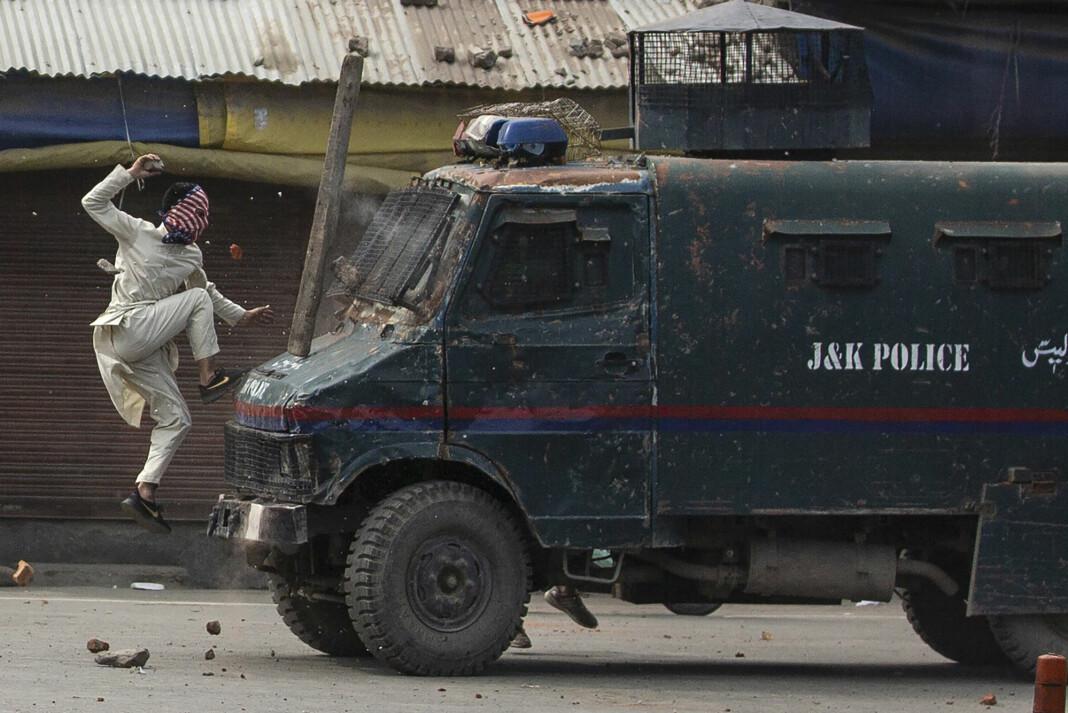 En maskert mann hopper mot et kjøretøy tilknyttet indisk politi i Kashmir i mai 2019. Bildet er tatt av fotografen Dar Yasin, som vant Pulitzer som bildene tatt fra området.