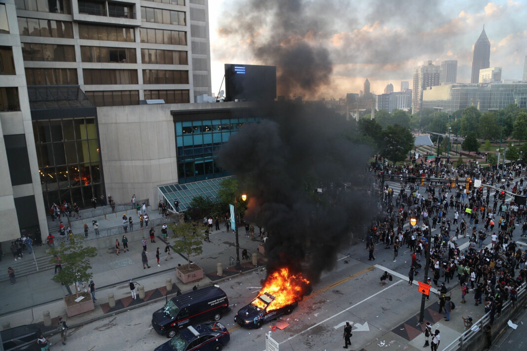 Demonstranter har satt fyr på en politibil i Atlanta i Georgi fredag.