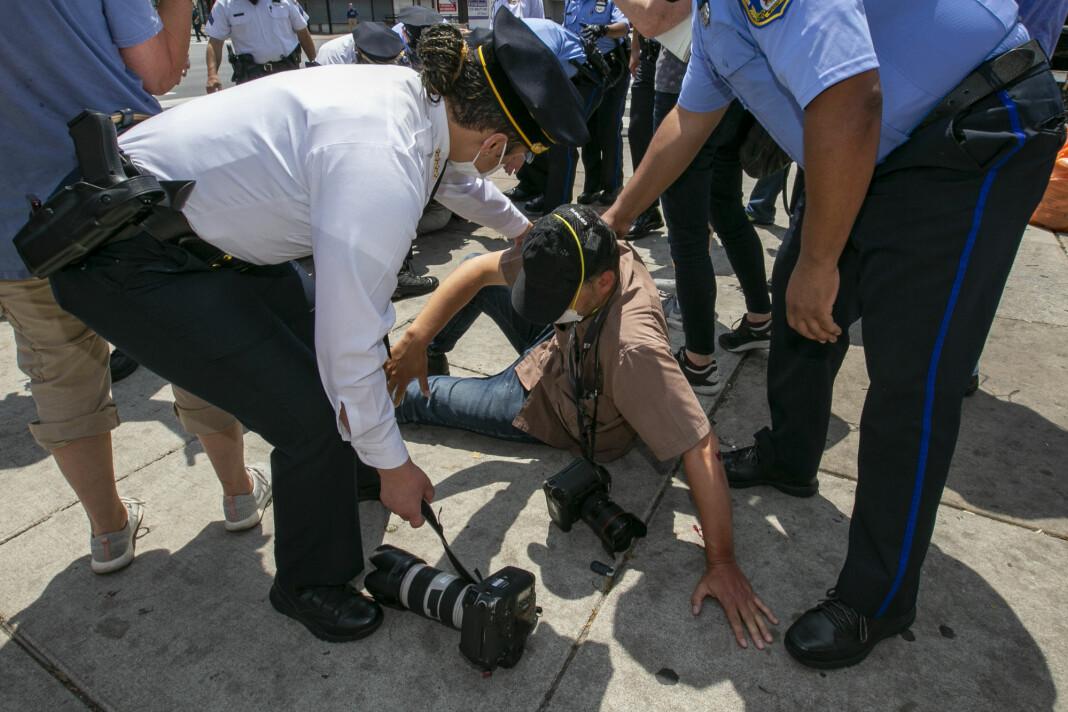 Politisjef Danielle Outlaw (t.v.) ser til AP-fotograf Matt Rourke etter at han ble angrepet av en tilfeldig forbipasserende i Philadelphia torsdag.