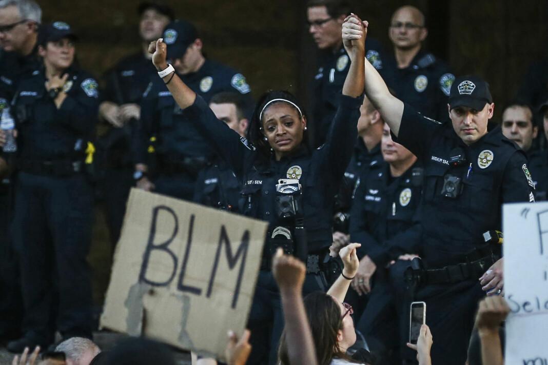 Politibetjent Alexandra Parker holder hendene til en kollega foran demonstranter i Austin fredag.