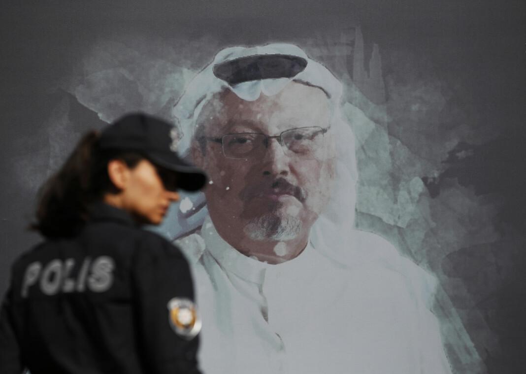 En tyrkisk politibetjent passerer et bilde av Jamal Khashoggi som er satt opp i forbindelse med en seremoni for den saudiarabiske journalisten og skribenten i Istanbul i forbindelse med årsdagen for drapet.