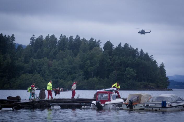 En AUF-ungdom blir fraktet bort på fastlandssiden ved Utøya. I bakgrunnen ser vi Utøya og helikopter fra forsvaret.
