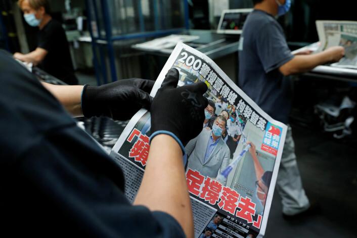 Apple Daily slo i dag opp at avisens eier er arrestert. Bildet viser Jimmy Lai i redaksjonslokalene sammen med politifolkene.