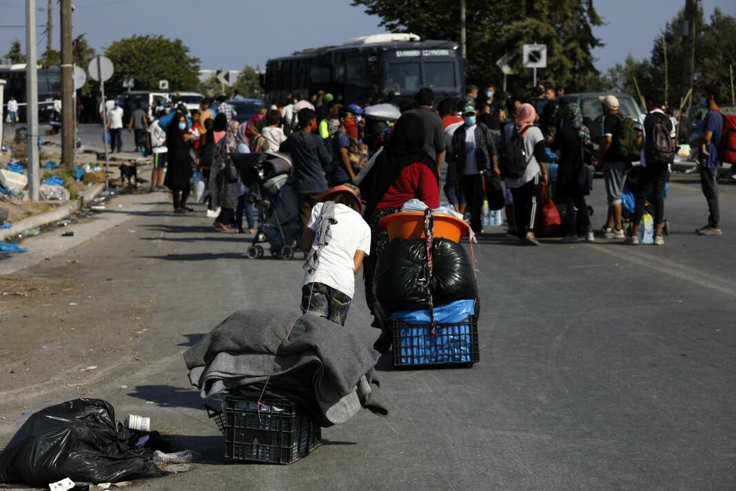 Asylsøkere frakter tingene sine på en vei utenfor Moria torsdag. Reportere uten grenser anklager gresk politi for å hindre journalister å dekke situasjonen.