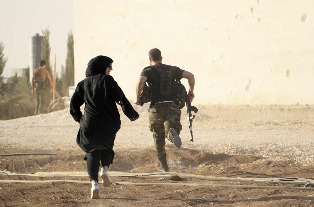 Kvinnelige reporter løper sammen med soldat for å unngå snikskyttere utenfor Aleppo i Syria i 2014.