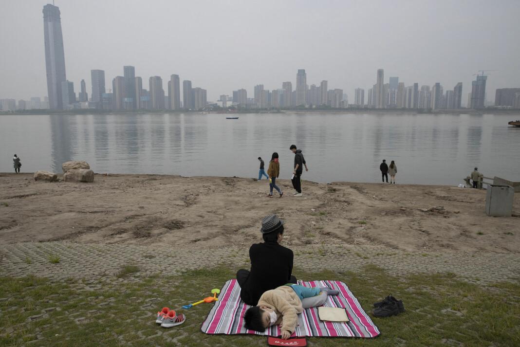 Folk lekte og slappet av ved breddene av Yangtze-elva i Wuhan i april. Byen var episenter for koronaviruset i februar, og flere borgerjournalister er fengslet for å ha rapportert fra byen i pandemiens tidligste dager.