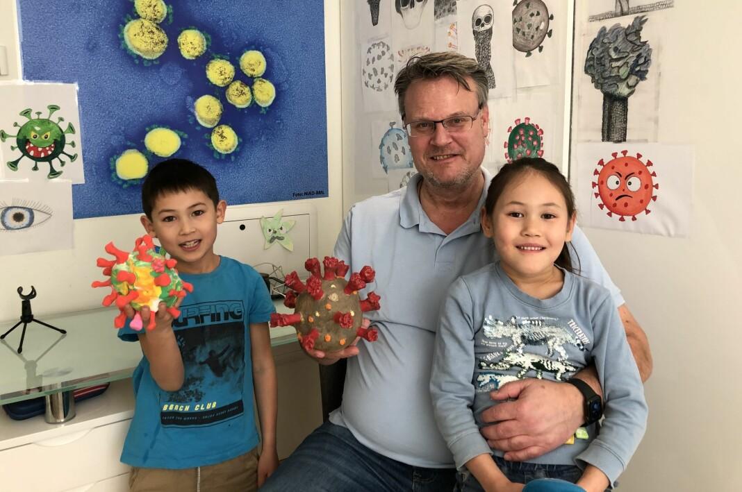 NRK-journalist Hallvard Sandberg med barna Odin og Freya, som har hjulpet pappa med å illustrere viruset.