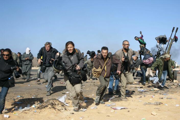 Journalister løper for å komme i dekning. Her er det Gaddafis fly som går til angrep.