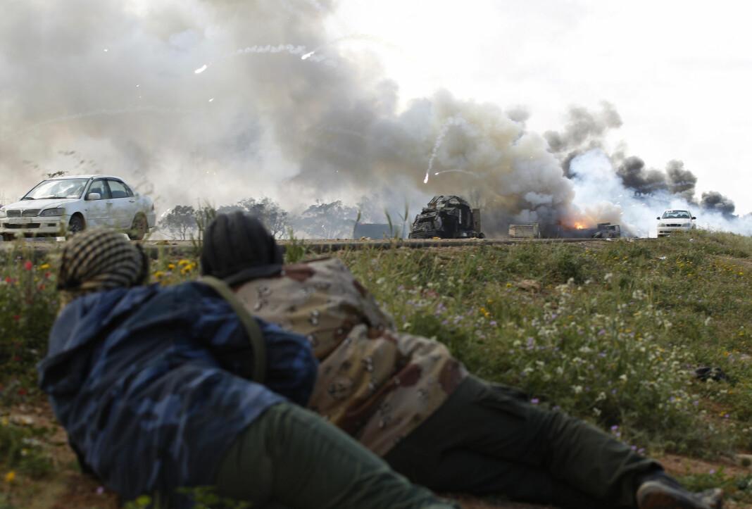 Opprørssoldater ligger i dekning og ser på at regjeringsstyrkene blir angrepet av fly. Bildet er fra 2011.