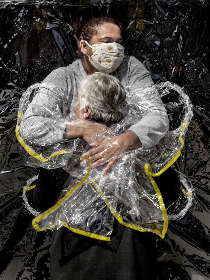 Fjorårets beste pressefoto ble tatt av den danske fotografen Mads Nissen i Brasil. Det viser 85 år gamle Rosa Luzia Lunardi som får en klem fra sykepleieren Adriana Silva da Costa Souza gjennom en gardin av gjennomsiktig plast på et pleiehjem i São Paulo.