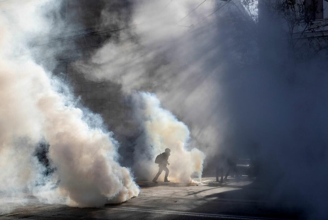 En fotograf løper vekk fra tåregassen under en koronademonstrasjon i Hellas tidligere i år.