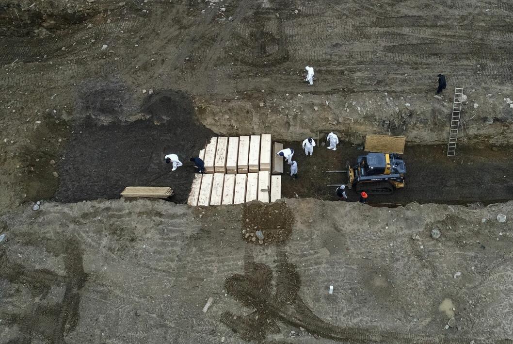 Dette bildet fra 9. april 2020 viser arbeidere som jobber med å gravlegge koronadøde personer på Hart Island utenfor New York City. Så langt er over 2400 personer gravlagt på øya, og man vurderer å gravlegge ytterligere 700 personer der ute.