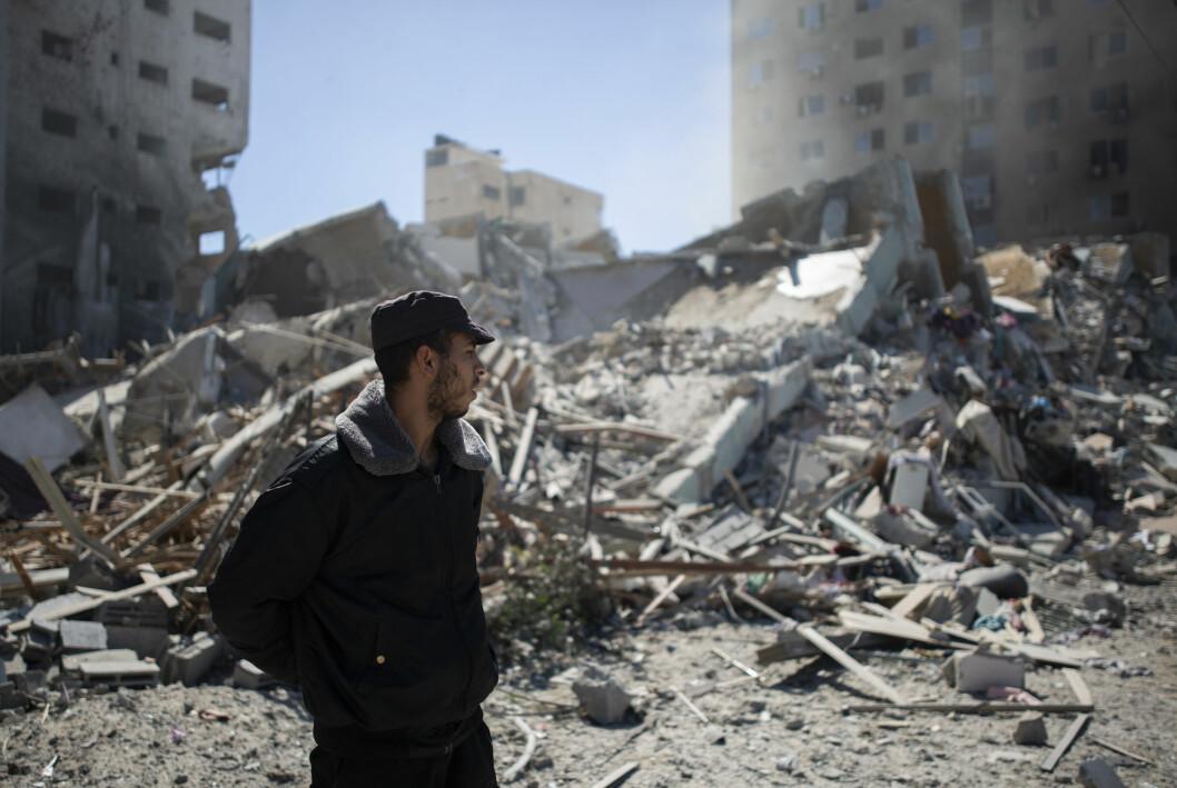 En palestinsk politimann står ved ruinene av høyhuset der en rekke internasjonale medier hadde sine kontorer i Gaza by. Høyhuset ble lagt i grus i et israelsk bombeangrep lørdag.
