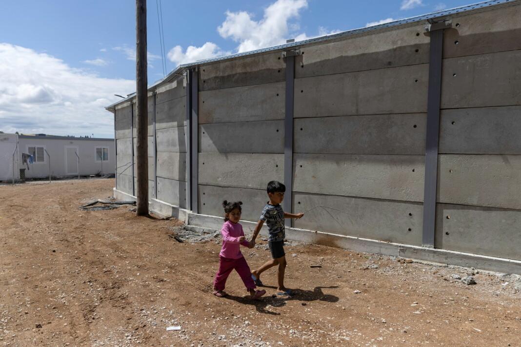 Barn går ved de nye betongmurene inne i flyktningleiren Ritsona i Hellas i juni 2021.
