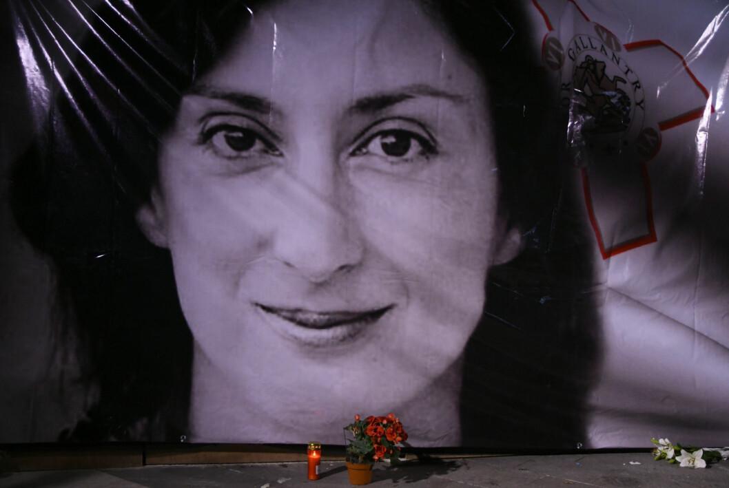 Blomster og lys foran et portrett av den drepte gravejournalisten Daphne Caruana Galizia utenfor et rettslokale i Valletta på Malta i 2018.