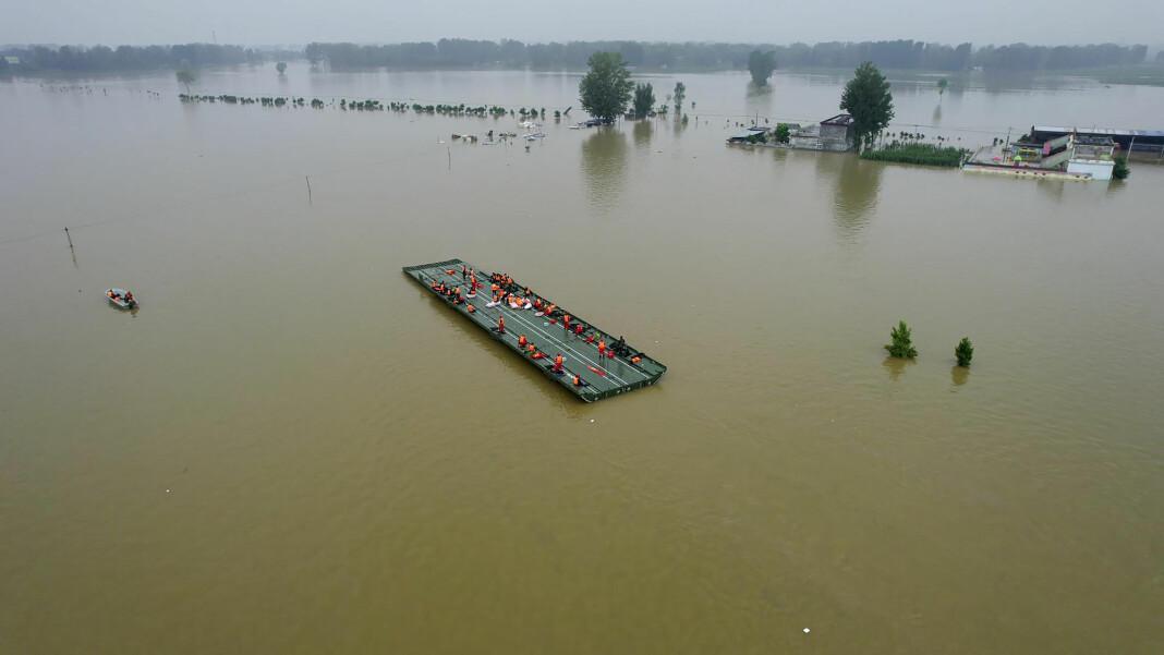 Redningsarbeidere er på vei for å redde folk som er rammet av flommen i Henan-provinsen i Kina.