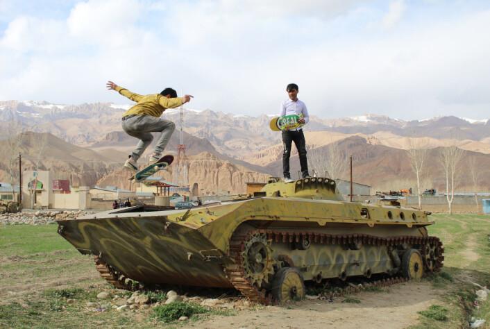 Feraidon og Mirza, to afghanske skatere fra Baymanprovinsen. Mirza lærer bort skating til barn av lavinntektsfamilier. Feraidon tar en Ollie (et skateboardtriks) på en tanks for å vise at vi ikke vil ha krig, og at det er på tide å jobbe for fred. Bildet er tatt i februar 2021.